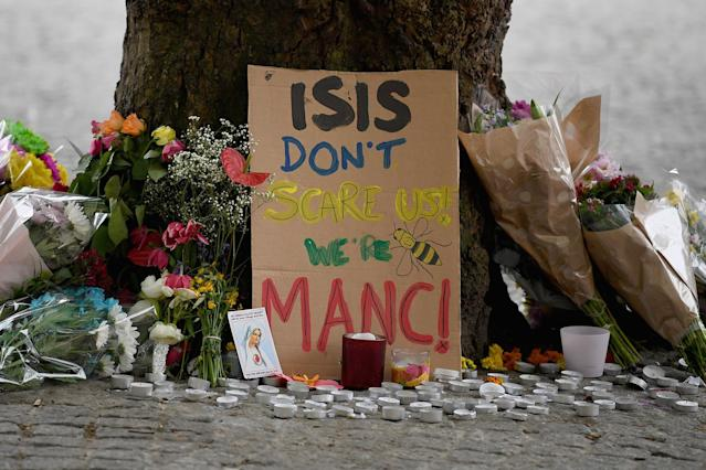 <p>Members of the public pause to look at floral tributes and messages as the working day begins on May 24, 2017 in Manchester, England. (Jeff J Mitchell/Getty Images) </p>