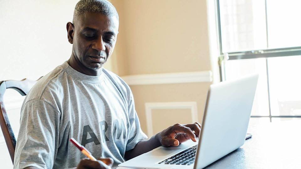 Black man using laptop and notebook at table.