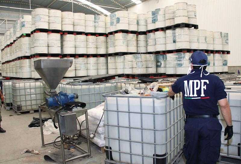 """FILE - In this June 20, 2011, photo released by Mexico's Attorney General's office, police from the Federal Public Ministry looks at drums of precursor chemicals for methamphetamine that were seized in Queretaro, Mexico. Mexican drug cartels are flooding U.S. cities with cheap, extraordinarily pure methamphetamine made in factory-like """"super labs"""" _ a surge in production that has all but negated the nation's long effort to curb meth production at home with tighter controls on key ingredients.(AP Photo/Attorney General's office, File)"""