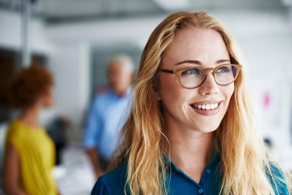 Thoughtful businesswoman smiling while looking away at creative office with colleagues in background