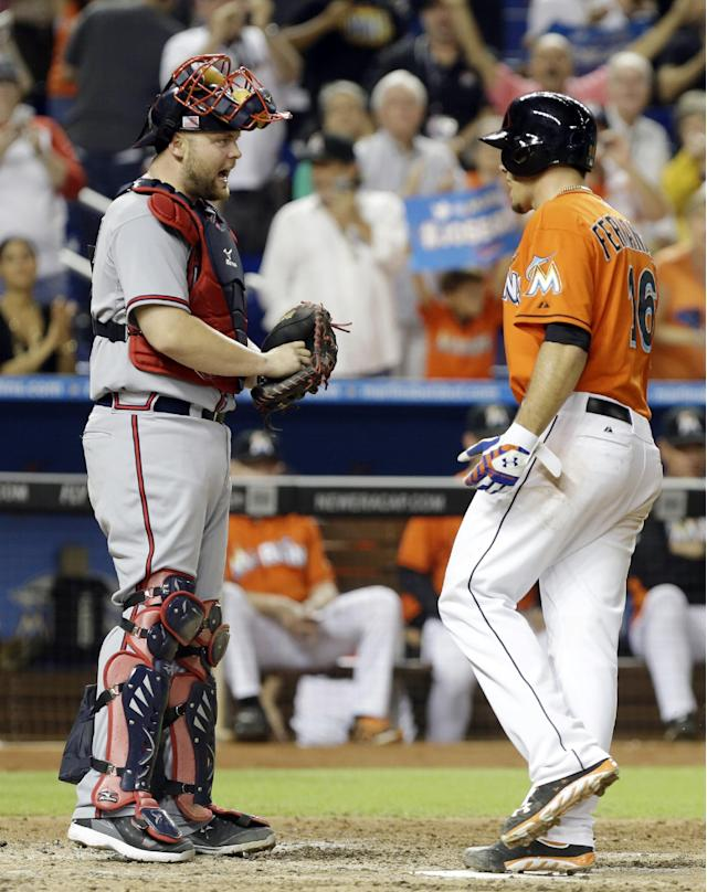 Atlanta Braves catcher Brian McCann, left, and Miami Marlins starting pitcher Jose Fernandez exchange words after Fernandez hit a solo home run in the sixth inning of a baseball game, Wednesday, Sept. 11, 2013, in Miami. (AP Photo/Lynne Sladky)