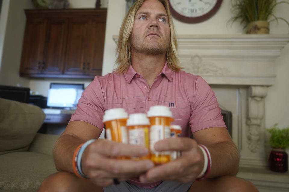 """David Stringham holds prescription bottles at his home Monday, Aug. 23, 2021, in Provo, Utah. Stringham says undergoing a procedure for shoulder and elbow pain at a local clinic in 2018 was """"the worst decision of my life"""" and left him in more pain. Since then, a neurologist has told Stringham he probably suffered nerve damage at the places where he was injected. (AP Photo/Rick Bowmer)"""