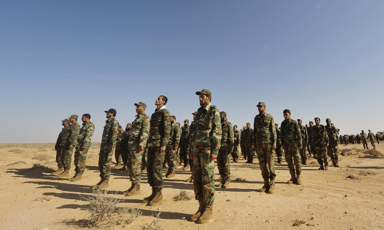 Trainee soldiers from the Libyan army stand at attention during their graduation exam in Geminis October 30, 2013. The trainees form the first batch of graduates who enlisted after the 2011 Libyan revolution. REUTERS/Esam Omran Al-Fetori (LIBYA - Tags: MILITARY)