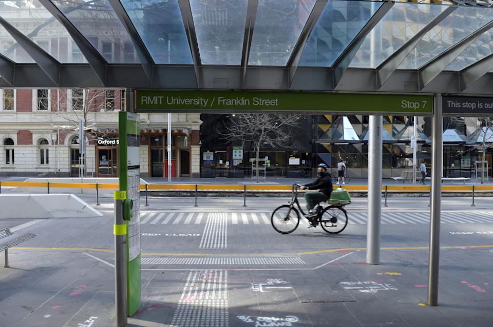 A delivery cyclist rides past the Royal Melbourne Institute of Technology (RMIT) University city campus in Melbourne, Australia.