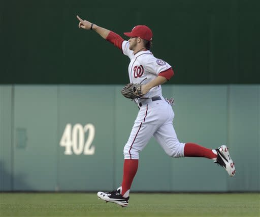 Washington Nationals left fielder Bryce Harper points to the crowd as he takes his position at the start of the Nationals' baseball game against the Arizona Diamondbacks at Nationals Park in Washington, Tuesday, May 1, 2012. (AP Photo/Susan Walsh)