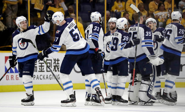 Winnipeg Jets left wing Nikolaj Ehlers, left, of Denmark, celebrates with defenseman Tyler Myers (57) after they defeated the Nashville Predators in Game 1 of an NHL hockey second-round playoff series Friday, April 27, 2018, in Nashville, Tenn. (AP Photo/Mark Humphrey)