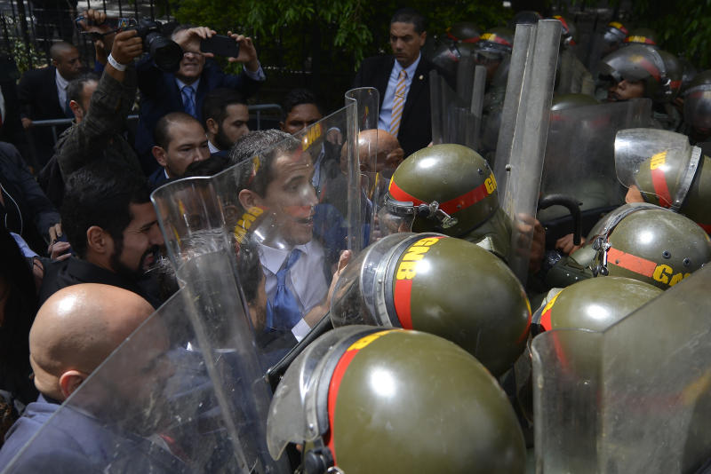 National Assembly President Juan Guaido, Venezuela's opposition leader, is blocked by National Guards from entering the compound of the Assembly, where he was to lead a session to elect new Assembly leadership in Caracas, Venezuela, Sunday, Jan. 5, 2020. With Guaido and his allies stuck outside, a rival slate headed by lawmaker Luis Parra swore themselves in as leaders of the single-chamber legislature. (AP Photo/Matias Delacroix)