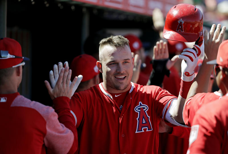 Los Angeles Angels' Mike Trout is congratulated by teammates on his three-run home run against the Chicago White Sox in the first inning of a spring training baseball game Friday, March 22, 2019, in Tempe, Ariz. (AP Photo/Elaine Thompson)