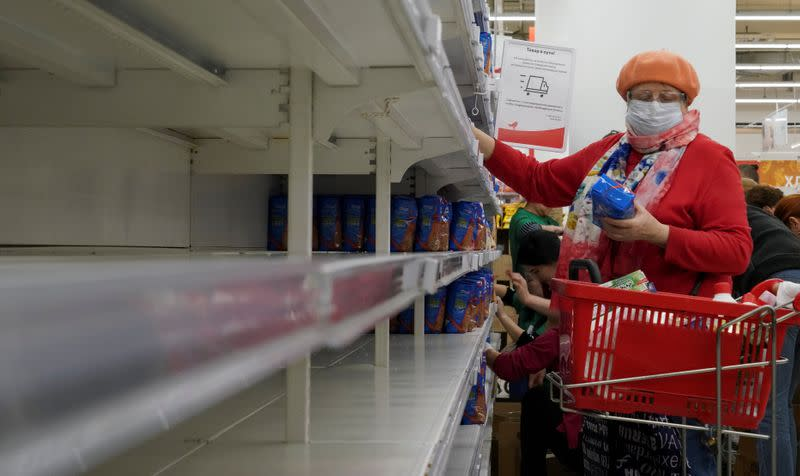 FILE PHOTO: A woman, wearing a protective mask, holds a pack of buckwheat from a new delivery, next to empty shelves in a section for cereals and groats, in a supermarket in Moscow