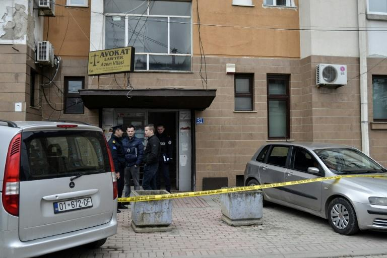 Kosovo's police officers stand at the bottom of the building where prominent lawyer, Azem Vllasi was wounded in an armed attack on March 13, 2017 in Pristina