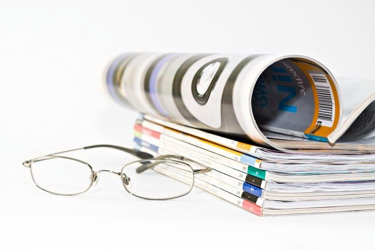 Pile of medical journals next to a pair of spectacles