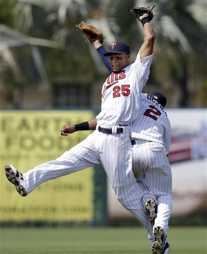 Minnesota Twins shortstop Pedro Florimon (25) hangs onto a pop fly by Toronto Blue Jays' Andy LaRoche, as teammate second baseman Brian Dozier (2) crashes into him during the fifth inning of an exhibition spring training baseball game in Fort Myers, Fla., Sunday March 24, 2013. (AP Photo/Elise Amendola)