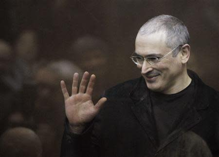 Jailed Russian former oil tycoon Mikhail Khodorkovsky waves as he stands in the defendants' cage before the start of a court session in Moscow in this December 27, 2010 file photograph. REUTERS/Denis Sinyakov/Files