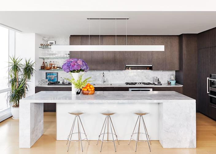 """A TV-watching nook in the kitchen's original design was converted into a wet bar, complete with vintage Baccarat crystal stemware and vintage <a href=""""https://www.gucci.com/us/en/"""" rel=""""nofollow noopener"""" target=""""_blank"""" data-ylk=""""slk:Gucci"""" class=""""link rapid-noclick-resp"""">Gucci</a> sterling-silver rope bar goblets. """"Who even sits and looks at a TV? You're looking at your phone, you have an iPad, whatever,"""" says Deutsch. """"We wanted to use that space as something so much more creative and beautiful to look at."""" The barstools are by Pepe Cortes for <a href=""""https://www.knoll.com/"""" rel=""""nofollow noopener"""" target=""""_blank"""" data-ylk=""""slk:Knoll"""" class=""""link rapid-noclick-resp"""">Knoll</a>. Flowers throughout their apartment were arranged by the couple's longtime fave florist, <a href=""""https://www.michaelgeorgeflowers.com/"""" rel=""""nofollow noopener"""" target=""""_blank"""" data-ylk=""""slk:Michael George"""" class=""""link rapid-noclick-resp"""">Michael George</a>."""
