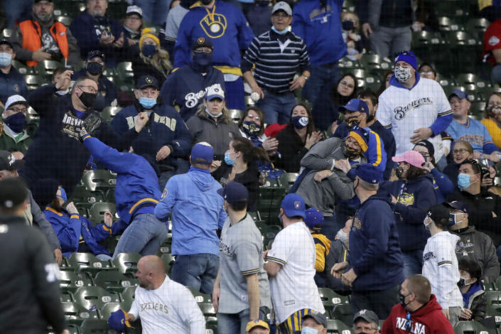 Fans watch a ball bounce into the stands during the third inning of an opening day baseball game between the Milwaukee Brewers and the Minnesota Twins on Thursday, April 1, 2021, in Milwaukee. (AP Photo/Aaron Gash)