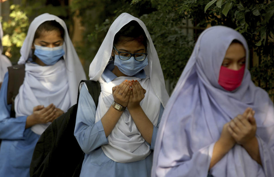 Students wearing face masks to prevent the spread of the coronavirus as they pray upon their arrival at their school, in Karachi, Pakistan, Monday, Jan. 18, 2021. Pakistani authorities started to reopen schools in phases despite a steady increase in deaths and infections from the coronavirus, official said. (AP Photo/Fareed Khan)
