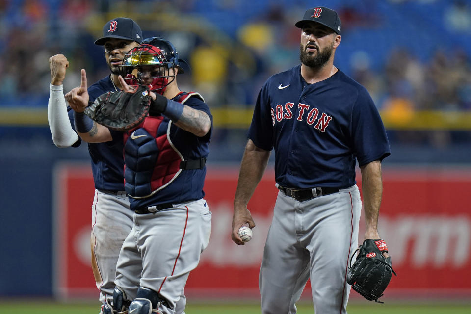 Boston Red Sox plyers, from left, third baseman Rafael Devers, catcher Christian Vazquez, and relief pitcher Brandon Workman react after Workman was called for a balk against the Tampa Bay Rays during the third inning of a baseball game Wednesday, June 23, 2021, in St. Petersburg, Fla. (AP Photo/Chris O'Meara)