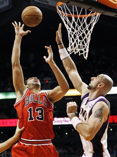 Chicago Bulls' Joakim Noah (13) goes up for a shot but misses as Phoenix Suns' Marcin Gortat, of Poland, defends during the first half of an NBA basketball game, Wednesday, Nov. 14, 2012, in Phoenix. (AP Photo/Ross D. Franklin)