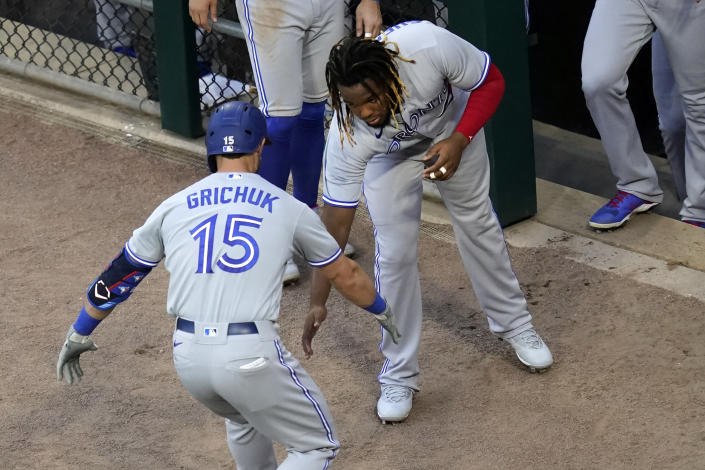 Toronto Blue Jays' Randal Grichuk celebrates his home run off Chicago White Sox starting pitcher Lance Lynn with Vladimir Guerrero Jr. during the second inning of a baseball game Wednesday, June 9, 2021, in Chicago. (AP Photo/Charles Rex Arbogast)