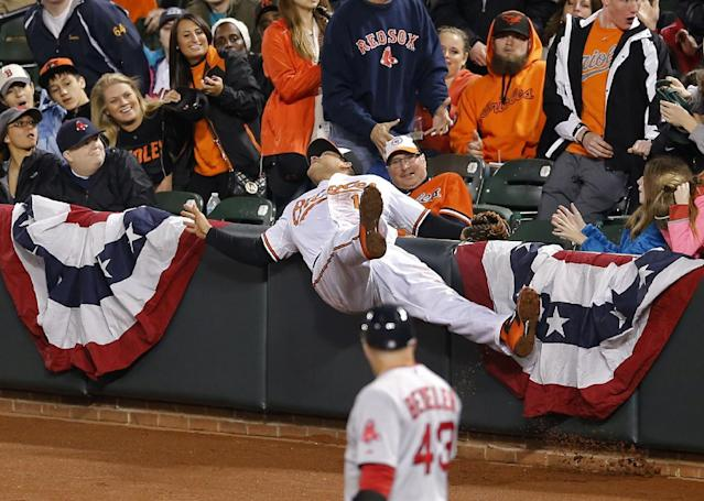 Baltimore Orioles first baseman Chris Davis collides with a wall as he tries but cannot make a catch on a pop fly hit by Boston Red Sox's Mike Napoli in the third inning of a baseball game on Thursday, April 3, 2014, in Baltimore. (AP Photo/Patrick Semansky)