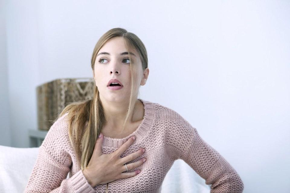 Woman pressing her chest.