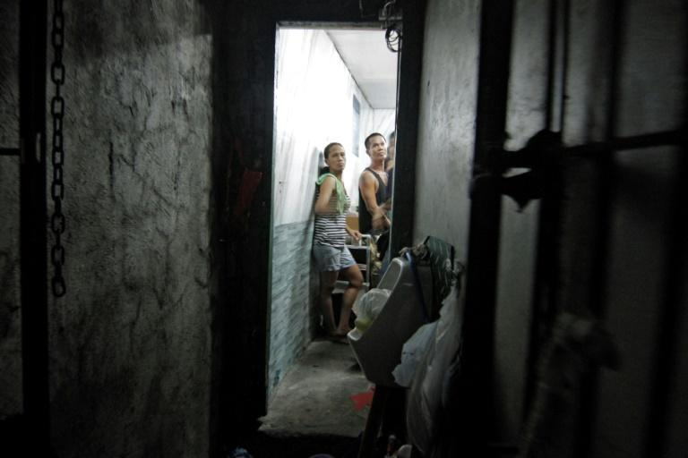 A dozen people have been found stuffed inside a closet-sized cell hidden behind a book shelf in a Philippine police station