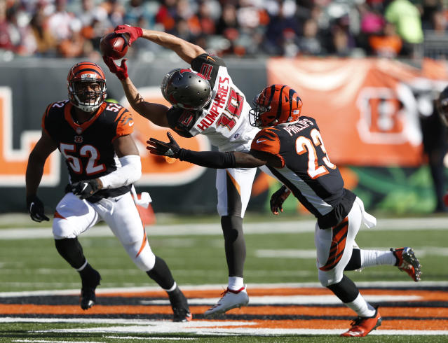FILE - In this Oct. 28, 2018,. file photo, Tampa Bay Buccaneers wide receiver Adam Humphries (10) makes a catch between Cincinnati Bengals cornerback Darius Phillips (23) and linebacker Preston Brown (52) during the second half of an NFL football game, in Cincinnati. For Adam Humphries, Tennessee has been a potential destination for months based on his relationship with Titans general manager Jon Robinson because of their Tampa Bay connection. Not even a late push by the New England Patriots could sway him to walk away from his deal with the Titans. Even considering how much success wide receivers like Humphries have enjoyed with the defending Super Bowl champs.Obviously, Im a man of my word, and Im going to keep my word there, Humphries said Thursday, March 14, 2019, after signing with Tennessee. (AP Photo/Frank Victores, File)