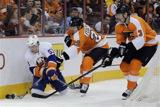 New York Islanders' Casey Cizikas, left, vies for the puck with Philadelphia Flyers' Ruslan Fedotenko, center, of Ukraine, and Kurtis Foster during the first period of an NHL hockey game Thursday, March 28, 2013, in Philadelphia. (AP Photo/Matt Slocum)
