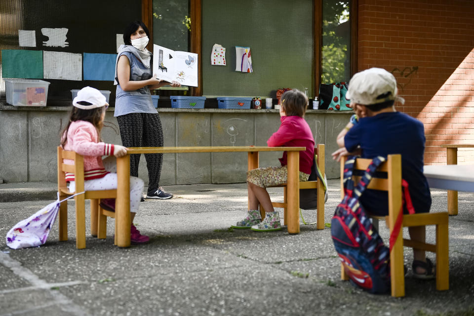 A teacher is seen reading a book to kindergarten children in a school garden in Turin, Italy, as part of a pilot test to see how schools can reopen after the coronavirus lockdown. Now schools in the U.S. are considering similar outdoor-classroom setups. (Photo: Nicolò Campo/LightRocket via Getty Images)