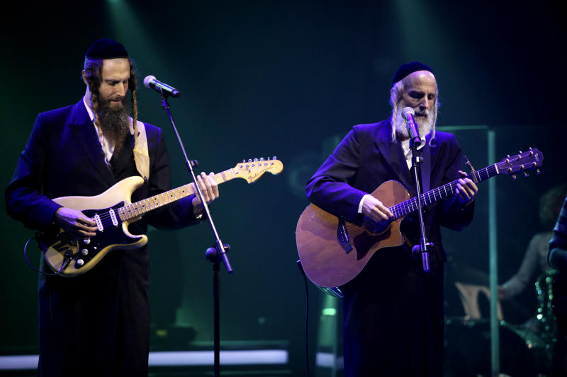 In this photo taken Oct. 22, 2013, Ultra-Orthodox Jewish singers Arie Gat, right, and his brother Gil, perform as they participate in an Israeli tv show in Neve Ilan, Jerusalem. For most Israelis, the common perception of the ultra-Orthodox Jewish minority is that of an insulated, segregated society devoted to studying ancient biblical texts and rejecting the ills of secular life. But the pair of devout, soft-spoken brothers in skullcaps and sidecurls are now breaking down some stereotypes by emerging as the most unlikely of media darlings _ reality rock stars. (AP Photo/Dan Balilty)