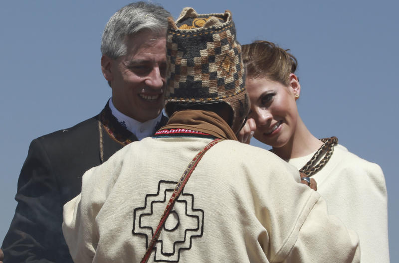 An Aymaran spiritual guide speaks to Bolivia's Vice President Alvaro Garcia Linera, left, and his bride Claudia Fernandez during their wedding ceremony at a temple of stone walls, in Tiwanaku, Bolivia, Saturday, Sept. 8, 2012. The ceremony uniting the 49-year-old vice president with the 25-year-old journalist was held at an ancestral site constructed by the ancient Aymara people some 3,000 years ago to observe the heavens. (AP Photo/Juan Karita)