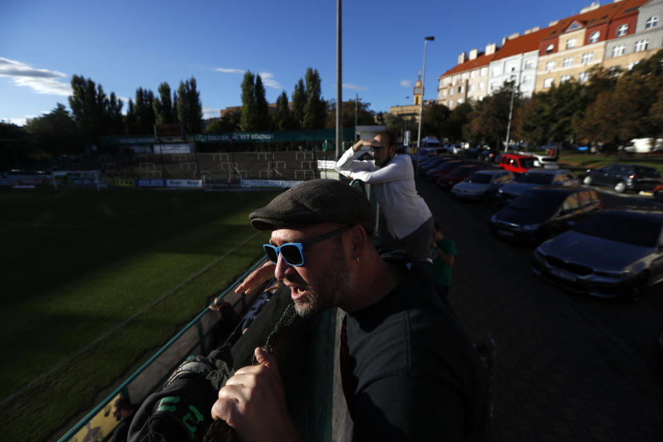 Fans, standing on ladders from behind the fence, watch a Czech first division match between Bohemians Prague and Zlin in Prague, Czech Republic, Sunday, Oct. 4, 2020. Amid restrictive measures that limit the number of soccer fans from attending the game, fans are looking for innovative ways to watch the match during the ongoing coronavirus pandemic. (AP Photo/Petr David Josek)