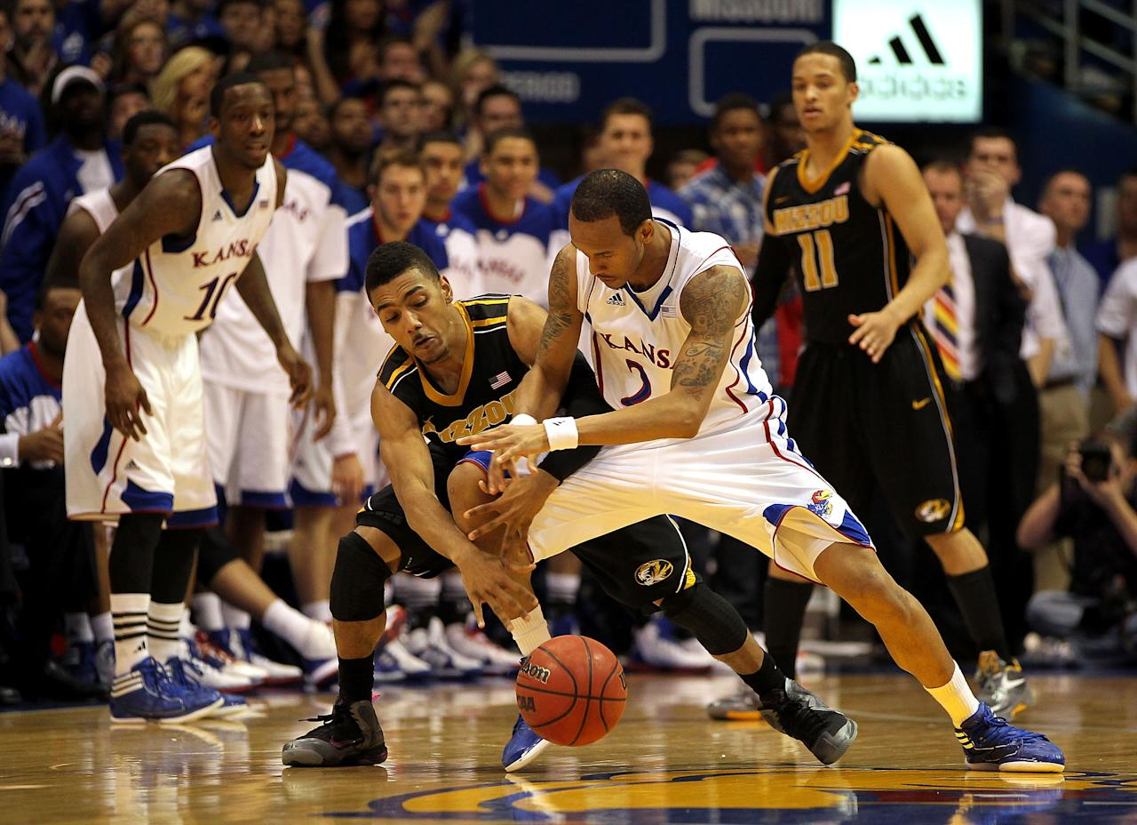 LAWRENCE, KS - FEBRUARY 25:  Travis Releford #24 of the Kansas Jayhawks and Phil Pressey #1 of the Missouri Tigers battle for a loose ball during the game on February 25, 2012 at Allen Fieldhouse in Lawrence, Kansas.  (Photo by Jamie Squire/Getty Images)