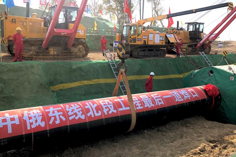 FILE PHOTO: Workers are seen at the construction site of a natural gas pipeline as part of China-Russia gas pipeline project in Heihe, Heilongjiang