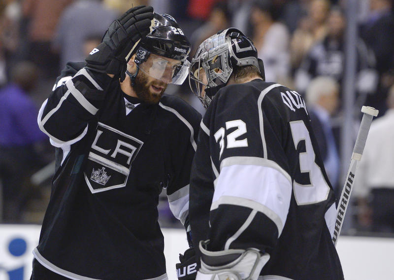 Los Angeles Kings center Jarret Stoll (28) congratulates goalie Jonathan Quick (32) after the Kings defeated the Chicago Blackhawks 3-1 in Game 3 of the NHL hockey Stanley Cup playoffs Western Conference finals, Tuesday, June 4, 2013, in Los Angeles. (AP Photo/Mark J. Terrill)