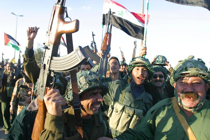 Militants of the ruling Baath party wave their rifles in the air and the Iraqi flag during training session on the main street of Baghdad's Saddam City neighboorhood 22 February 2003 (AFP Photo/Karim Sahib)