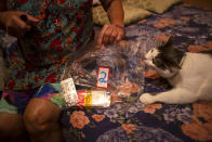 """Diana dos Santos, 71, holds a bag of medicine numbered by her relatives to help her keep track of the times she needs to take her medications, as her pet cat Pepinha sniffs the bag, in her home in Rio de Janeiro, Brazil, Friday, Aug. 27, 2021, amid the new coronavirus pandemic. Dos Santos is diabetic and was hospitalized for a heart condition. She refuses to leave home until she gets her booster of the COVID-19 vaccine. """"I can't go out like before and I'm still afraid of all of this,"""" dos Santos said. """"I will feel safer (with a booster)."""" (AP Photo/Bruna Prado)"""