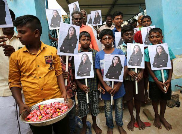 PHOTO: A child holds a tray of chocolates as others hold portraits of U.S. Vice President-elect Kamala Harris after participating in special prayers ahead of her inauguration, at a Hindu temple in Thulasendrapuram, India, on Wednesday, Jan. 20, 2021.  (Aijaz Rahi/AP)