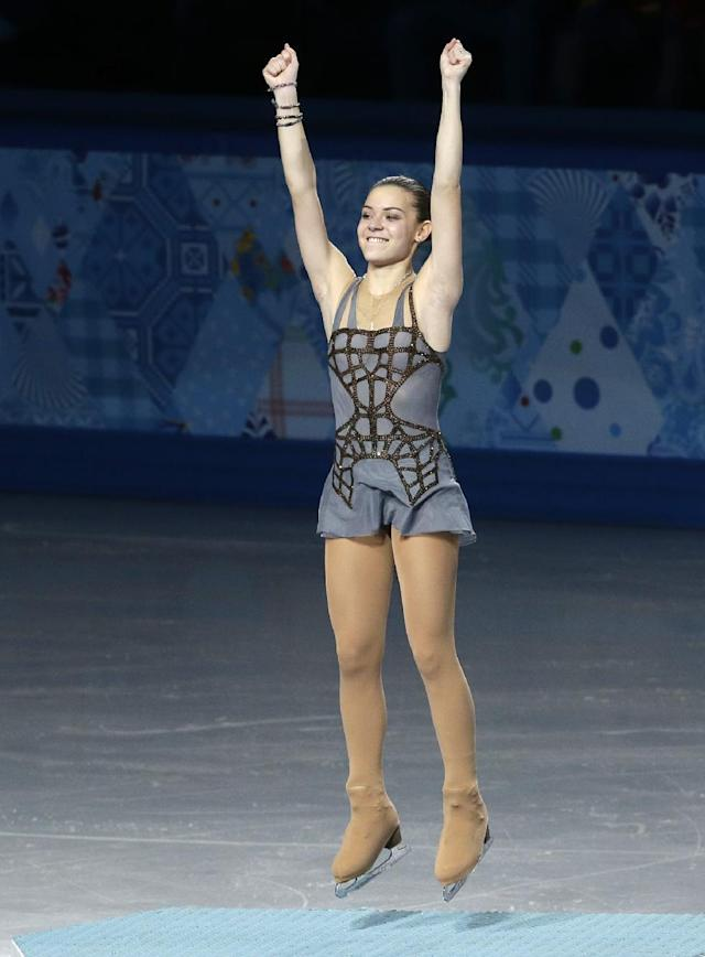 Adelina Sotnikova of Russia jumps on the podium as she celebrates placing first during the flower ceremony for the women's free skate figure skating final at the Iceberg Skating Palace during the 2014 Winter Olympics, Thursday, Feb. 20, 2014, in Sochi, Russia. (AP Photo/Darron Cummings)