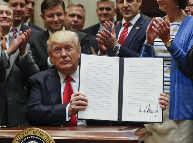 U.S. President Donald Trump displays an Executive Order on
