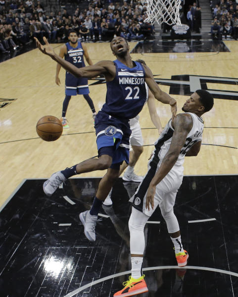 Minnesota Timberwolves guard Andrew Wiggins (22) is blocked by San Antonio Spurs forward Rudy Gay (22) as he tries to score during the first half of an NBA basketball game, Wednesday, Oct. 17, 2018, in San Antonio. (AP Photo/Eric Gay)