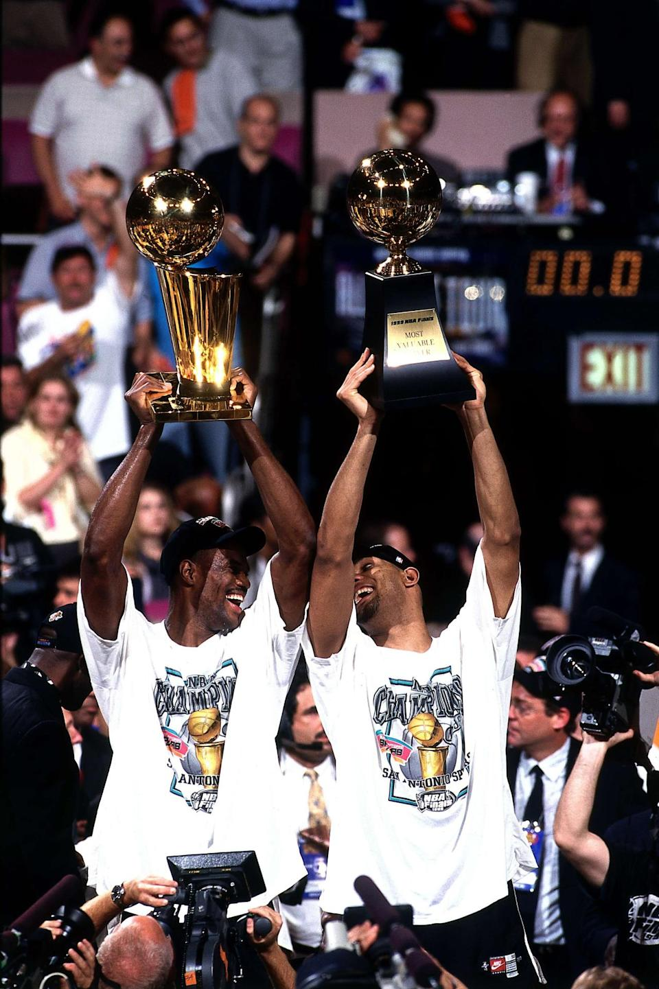 <p>1999: David Robinson #50 holds up the NBA Championship trophy as Tim Duncan #21 of the San Antonio Spurs holds up the MVP after winning Game Five of the 1999 NBA Finals at Madison Square Garden on June 25, 1999 in New York City, New York.</p>