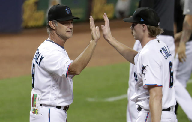 Miami Marlins manager Don Mattingly, left, high-fives relief pitcher Adam Conley after the Marlins defeated the Los Angeles Dodgers 13-7 in a baseball game, Thursday, Aug. 15, 2019, in Miami. (AP Photo/Lynne Sladky)