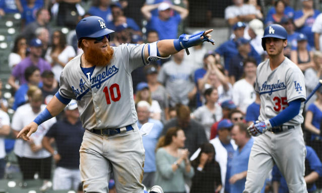 Los Angeles Dodgers' Justin Turner (10) points to Kyle Farmer after scoring during the ninth inning of a baseball game against the Chicago Cubs, Tuesday, June 19, 2018, in Chicago. (AP Photo/Matt Marton)