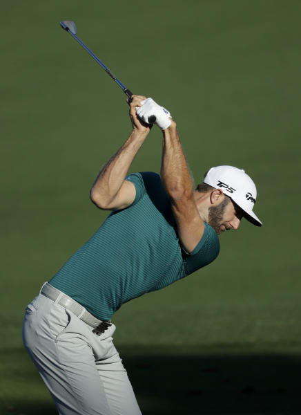 FILE - In this Tuesday, April 4, 2017, file photo, Dustin Johnson hits on the driving range during practice for the Masters golf tournament, in Augusta, Ga. The world's No. 1-ranked player was forced to withdraw from the Masters on Thursday because of a lower back injury suffered less than 24 hours earlier in a freak fall at the home he was renting for the week. (AP Photo/Matt Slocum, File)
