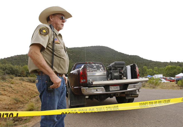 <p>Gila County Sheriff's Office deputy Larry Hassinger stands watch at the entrance to the First Crossing recreation area during a search and rescue operation for victims of a flash flood along the banks of the East Verde River, Sunday, July 16, 2017, in Payson, Ariz. (AP Photo/Ralph Freso) </p>