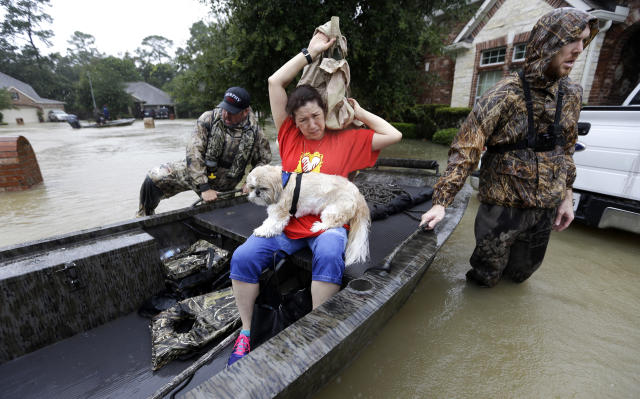 <p>Tina Cross puts on a jacket as her dog Mitzy sits her lap while being evacuated as floodwaters from Tropical Storm Harvey rise Aug. 28, 2017, in Spring, Texas. (Photo: David J. Phillip/AP) </p>