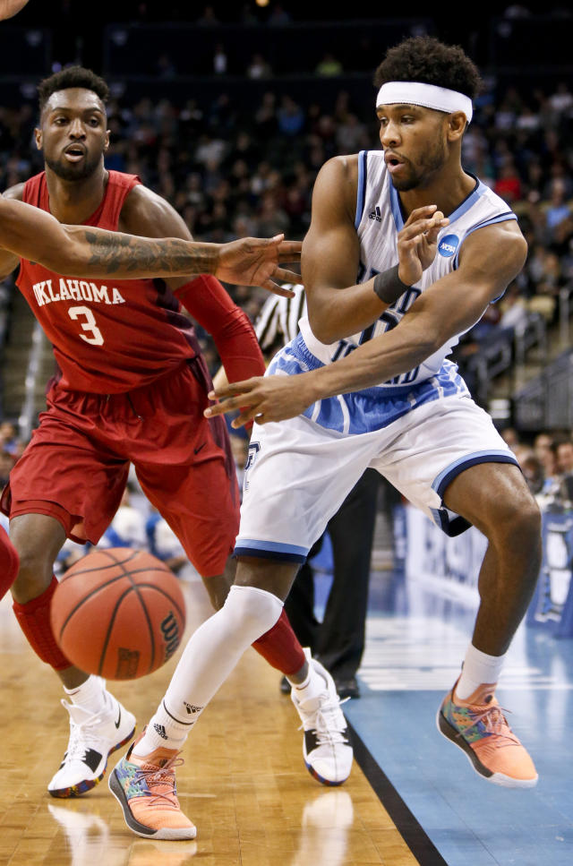 Rhode Island's E.C. Matthews, right, tries to keep the ball in bounds as Oklahoma's Khadeem Lattin (3) defends during the first half of an NCAA men's college basketball tournament first-round game, Thursday, March 15, 2018, in Pittsburgh. (AP Photo/Keith Srakocic)