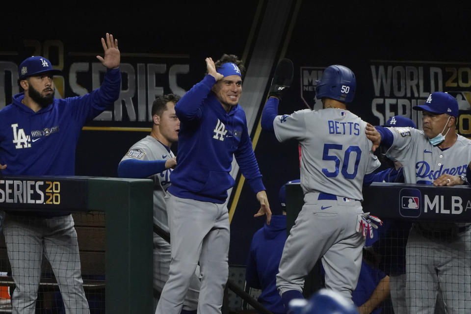 Los Angeles Dodgers' Mookie Betts celebrates at the dugout after scoring on a hit by Corey Seager during the first inning in Game 5 of the baseball World Series against the Tampa Bay Rays Sunday, Oct. 25, 2020, in Arlington, Texas. (AP Photo/Tony Gutierrez)