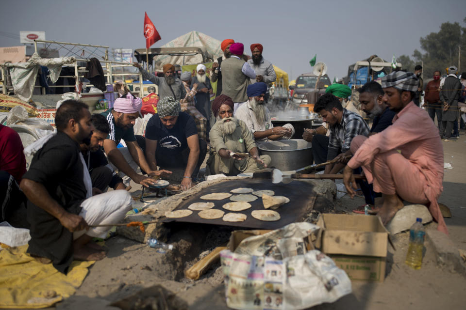 "Protesting farmers prepare flat bread for fellow farmers as they block a major highway during a protest against new farming laws they say will result in exploitation by corporations, eventually rendering them landless, at the Delhi-Haryana state border, India, Tuesday, Dec. 1, 2020. The busy, nonstop, arterial highways that connect most northern Indian towns to this city of 29 million people, now beat to the rhythm of never-heard-before cries of ""Inquilab Zindabad"" (""Long live the revolution""). Tens and thousands of farmers, with colorful distinctive turbans and long, flowing beards, have descended upon its borders where they commandeer wide swathes of roads. (AP Photo/Altaf Qadri)"